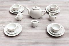 Tazas con los platillos y juego de té en la tabla marrón gris Foto de archivo libre de regalías