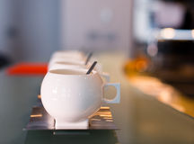Tazas contemporáneas de la porcelana blanca con los platillos a del acero inoxidable Foto de archivo libre de regalías