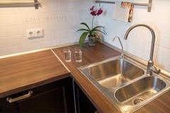 Tazas de agua en encimera en cocina moderna Foto de archivo libre de regalías