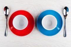 Tazas de café azules y rojas vacías con los platillos y las cucharas Fotografía de archivo
