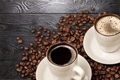 Tazas de café caliente con las habas en fondo de madera Imagenes de archivo