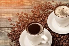 Tazas de café caliente con las habas en la tabla de madera Foto de archivo