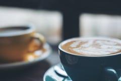 Tazas de café caliente del latte y de café de Americano en la tabla de madera del vintage Foto de archivo libre de regalías