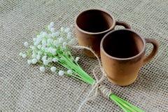 Tazas de café de cerámica de Brown y un ramo de lirio de los valles fragante del bosque en la arpillera foto de archivo libre de regalías