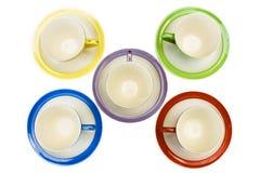 Tazas de café coloreadas con los platillos Fotos de archivo libres de regalías