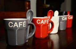 Tazas de café coloreadas en la tabla Fotos de archivo libres de regalías