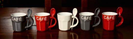 Tazas de café coloreadas en la tabla Imagen de archivo libre de regalías