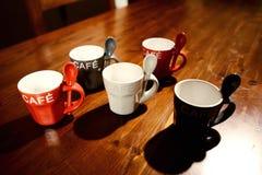 Tazas de café coloreadas en la tabla de madera Imagenes de archivo