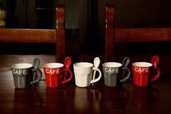 Tazas de café coloreadas en la tabla de madera Fotos de archivo libres de regalías