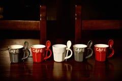 Tazas de café coloreadas en la tabla de madera Imágenes de archivo libres de regalías