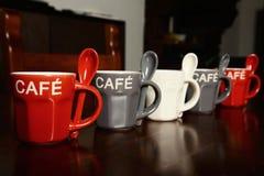 Tazas de café coloreadas en la tabla de madera Fotos de archivo