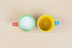 Tazas de café coloridas en el tablero de madera Imagenes de archivo