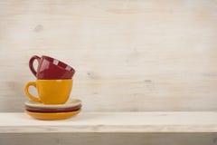 Tazas de café coloridas en estante sobre fondo de madera fotos de archivo libres de regalías