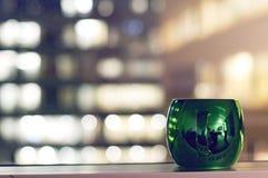 Tazas de café coloridas y estacionales con la ventana y las luces borrosas Fotografía de archivo