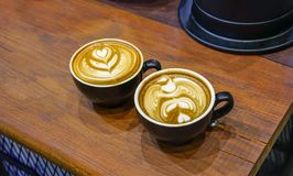 Tazas de café con arte hermoso del Latte en la tabla de madera Fotografía de archivo libre de regalías