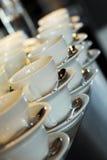 Tazas de café con las cucharas en un restaurante Imagenes de archivo