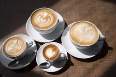 Tazas de café con las imágenes del caramelo en espuma Foto de archivo libre de regalías