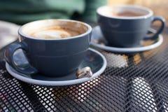 Tazas de café con los anillos de bodas Imagenes de archivo