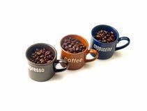Tazas de café con los granos de café Imagenes de archivo