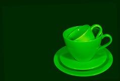 Tazas de café de cerámica del verde vivo con los platillos en fondo verde oscuro Imagen de archivo