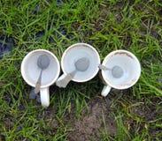 Tazas de café de cerámica diry blancas con las cucharas antes de lavarse Foto de archivo libre de regalías