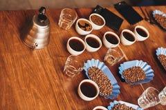 Tazas de café, de habas, y de caldera en la tabla para probar Foto de archivo