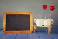 Tazas de café de los pares al lado de la pizarra vacía Fotografía de archivo