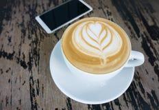 Tazas de café del arte del latte en la tabla de madera Fotos de archivo