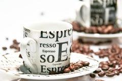 Tazas de café del café express entre el grano de café Foto de archivo