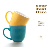 Tazas de café en azul y amarillo en el fondo blanco con Copyspace Imagen de archivo