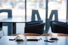 Tazas de café en los platillos y los dispositivos digitales en la tabla de madera en café Fotos de archivo libres de regalías