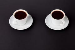 Tazas de café en un fondo negro Foto de archivo libre de regalías
