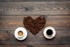 Tazas de café fuerte y lechoso recientemente preparado cerca de habas en forma del corazón en copyspace de madera oscuro de la op Fotos de archivo libres de regalías
