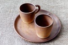 Tazas de café de la arcilla y plato de cerámica hecho a mano en un fondo casero áspero del yute foto de archivo libre de regalías