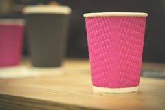 Tazas de café negras y rosadas del papel del arte en café en la tabla de madera Forma de vida, concepto del coffeeshop Imagen de archivo libre de regalías
