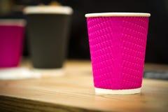 Tazas de café negras y rosadas del papel del arte en café en la tabla de madera Forma de vida, concepto del coffeeshop Fotografía de archivo libre de regalías