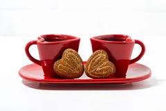 tazas de café rojas y galletas en forma de corazón en el fondo blanco Fotos de archivo