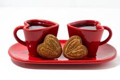 tazas de café rojas y galletas en forma de corazón en el fondo blanco Imagen de archivo libre de regalías