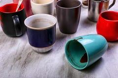 Tazas de café sucias vacías de diversos colores en la tabla Concepto de droga del cafeína, falta de energía y espera larga Copie  imágenes de archivo libres de regalías