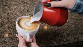 Tazas de café y granos de café frescos alrededor Barista Prepares Coffee Preparación del latte Barista que vierte la leche calien almacen de video