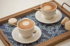 Tazas de café y de macarrones Imagen de archivo libre de regalías