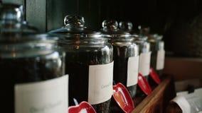 Tazas de caf? y granos de caf? frescos alrededor tarros y envases de té, cámara del movimiento metrajes