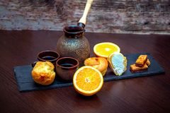 Tazas de cerámica, café que prepara el pote, naranja, profiterole o tortas y caramelos del eclair imagenes de archivo