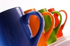 Tazas de cerámica multicoloras sobre blanco Fotos de archivo libres de regalías