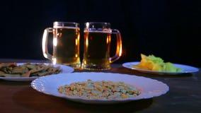 Tazas de cerveza con la cerveza de la espuma en un fondo negro en una tabla de madera con bocados en luz del color almacen de metraje de vídeo
