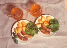 Tazas de cerveza con las placas de salchichas asadas a la parrilla Visión superior Imagen de archivo