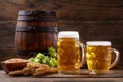 Tazas de cerveza con los saltos y los oídos verdes del trigo Imagen de archivo libre de regalías