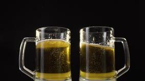 Tazas de cerveza que tintinean con la cerveza de oro ligera en la cámara lenta, cerveza de consumición con el amigo, burbujas en  almacen de metraje de vídeo