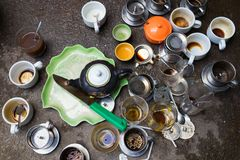 Tazas de consumición sucias drinkiMessy del café del café sucio sucio en las tazas del groundng en la tierra Fotografía de archivo libre de regalías