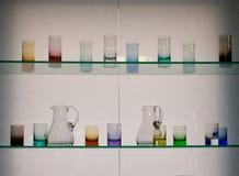 Tazas de cristal en dos estantes de cristal Fotos de archivo